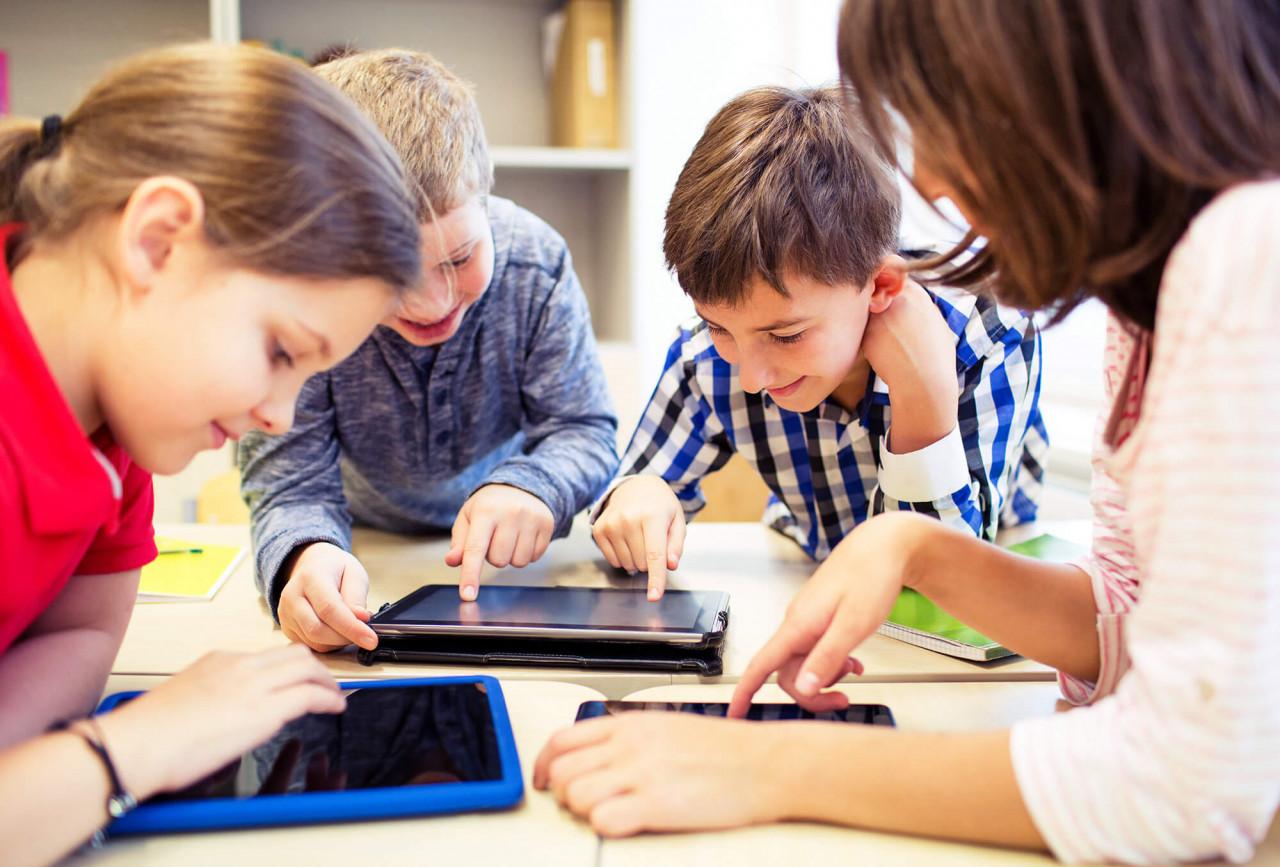 Fire skolebørn ved bord med tablets