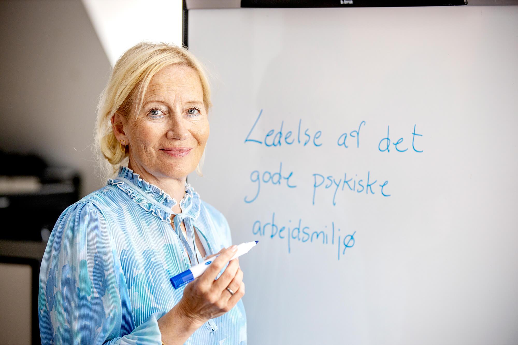 """Underviser skriver på tavle """"ledelse af det gode psykiske arbejdsmiljø"""""""