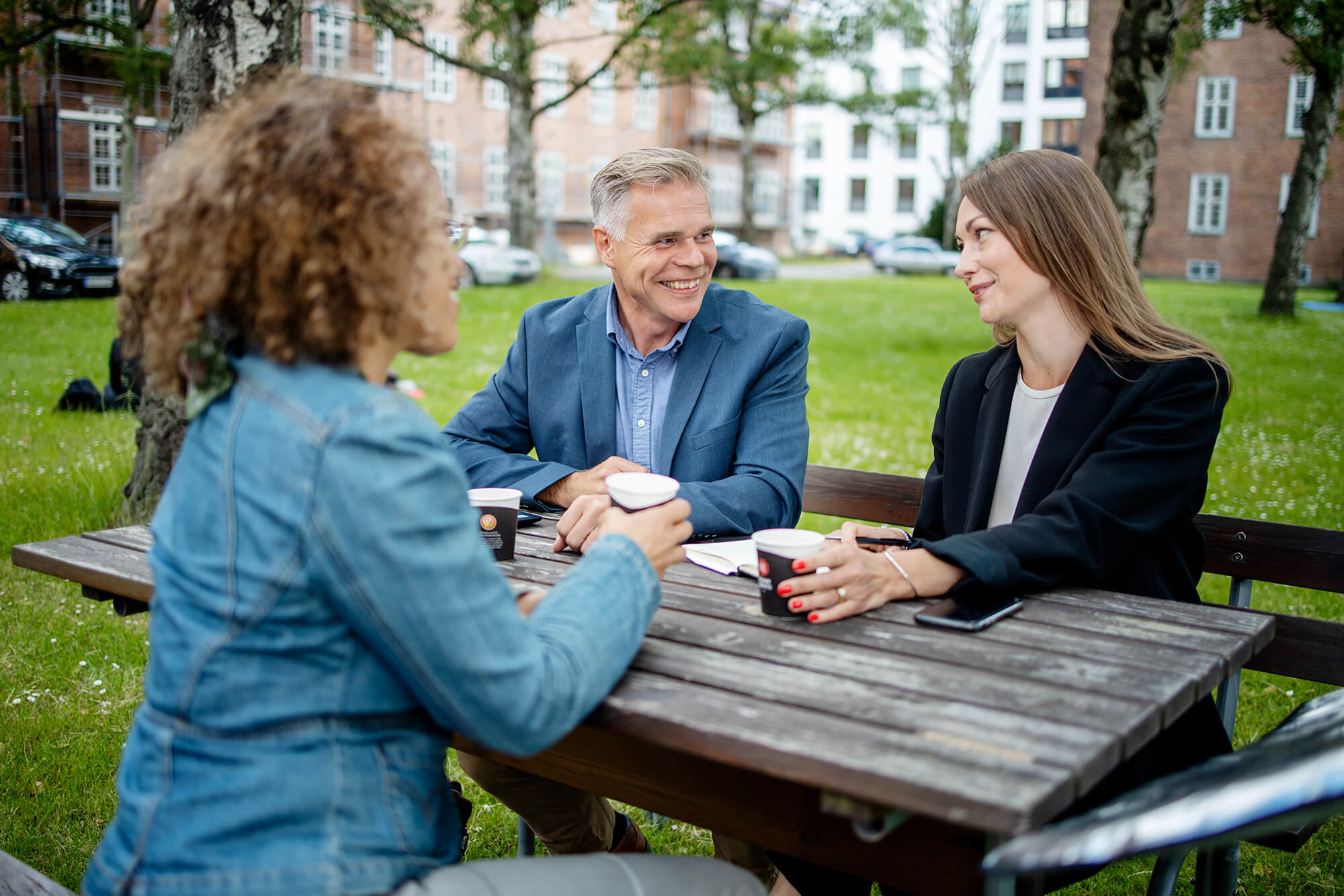 To kvinder og en mand i gruppearbejde udendørs