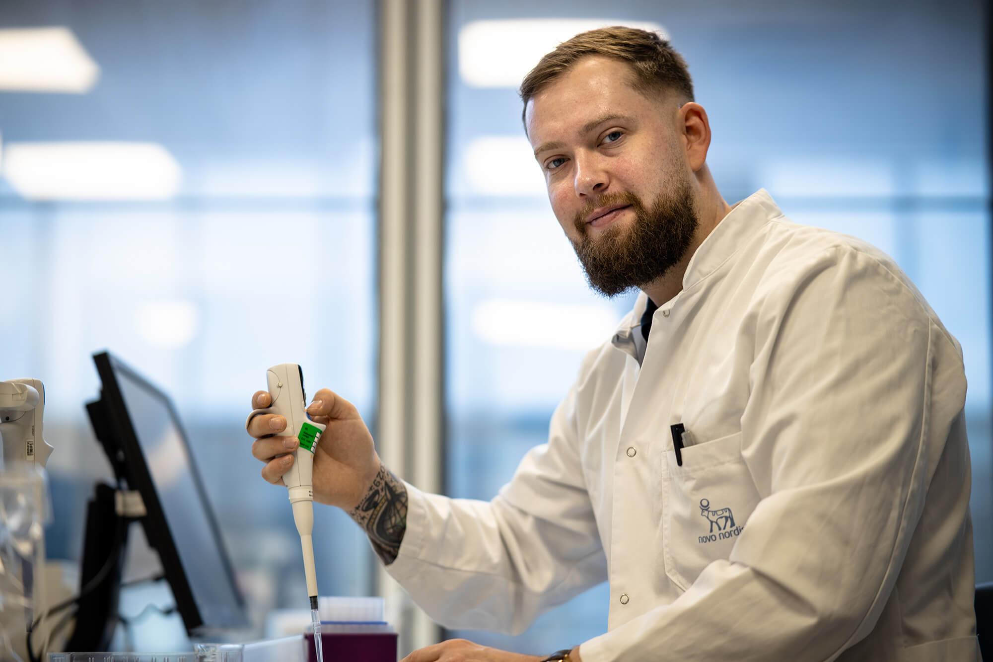 Mand med kittel arbejder i laboratorium