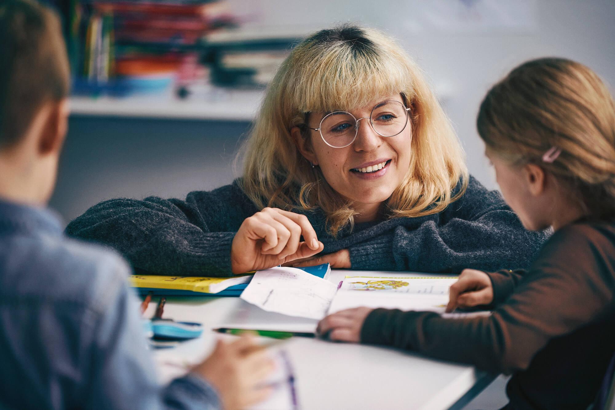 Lærer med to elever ved bord